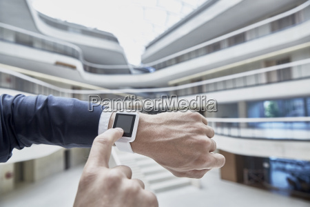 businessman touching smartwatch in office building