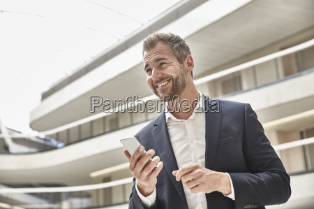 smiling businessman in office building holding