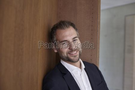 portrait of smiling businessman at wooden