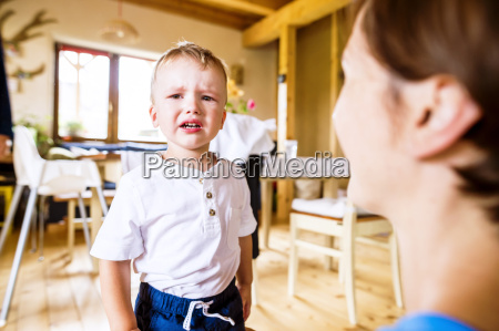 crying boy standing in kitchen with
