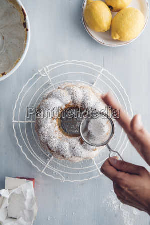 womans hands sprinkling icing sugar on