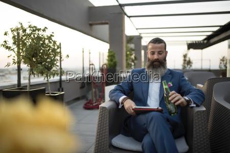 bearded businessman sitting on roof terrace