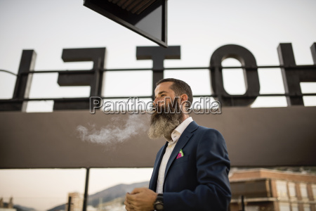 bearded businessman smoking cigarette on roof