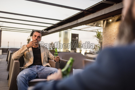 man with beer bottle sitting on