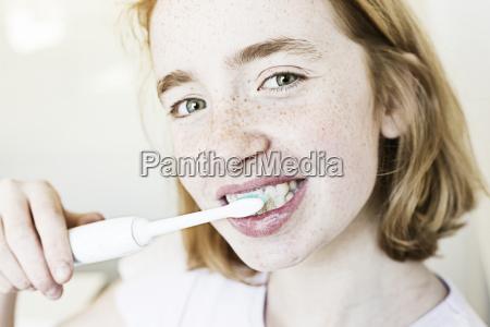 portrait of smiling girl brushing teeth