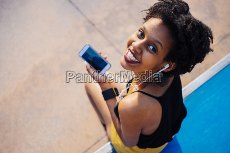 smiling young woman with earphones and