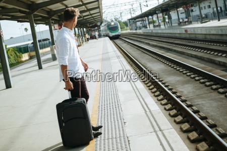 junger mann mit dem koffer am