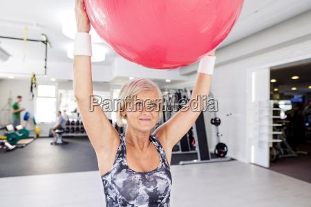 mature woman lifting up fitness ball