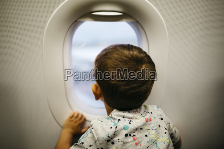 little boy looking out of airplane