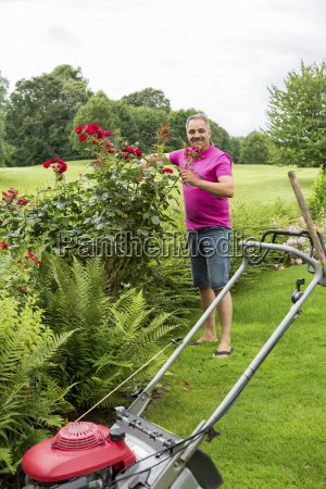 smiling man caring for his roses