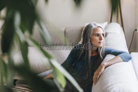 pensive woman sitting on the couch