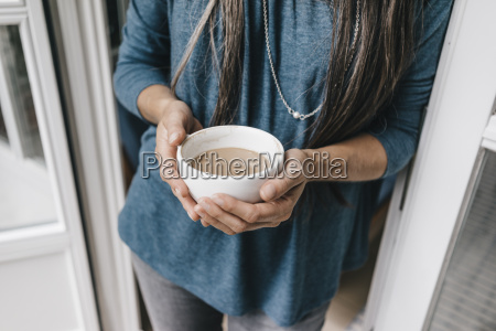 womans hands holding bowl of white