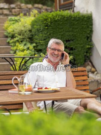 portrait of laughing senior man sitting