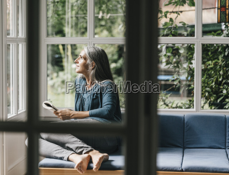 relaxed woman sitting with book on