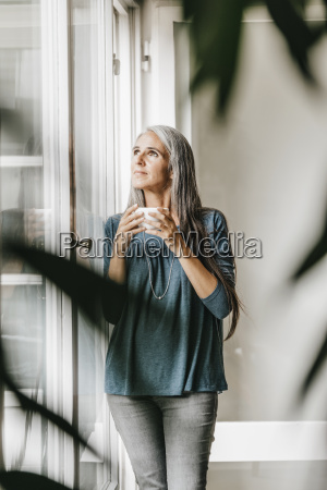 woman with bowl of coffee looking