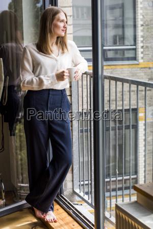 woman with coffee mug standing at