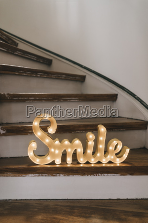 shining word smile on wooden steps