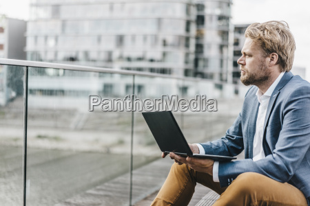 businessman sitting on bridge using laptop