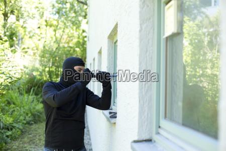 einbrecher mit crowbar breaking fenster