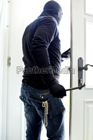 einbrecher mit perlenkette in taschenabgang