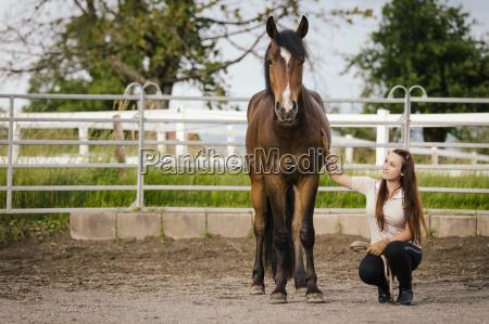 junge frau mit braunem pferd in