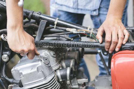 close up of woman repairing motorbike