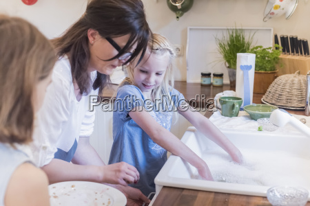 mother and two girls washing the