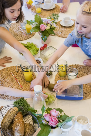 girls reaching for food on laid