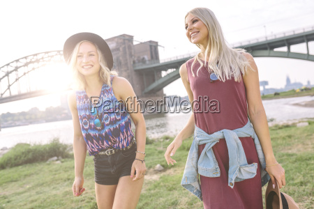two smiling young women walking at