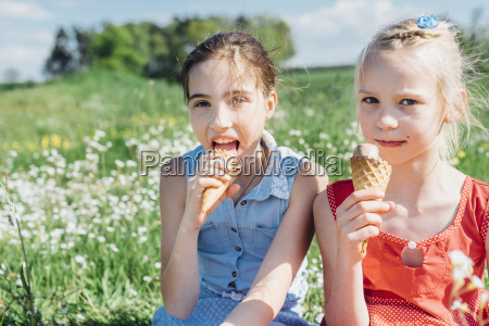 two girls in meadow eating ice