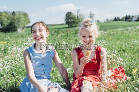 two girls in meadow with ice
