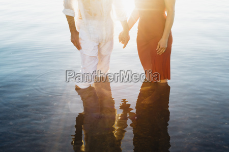couple holding hands standing in water