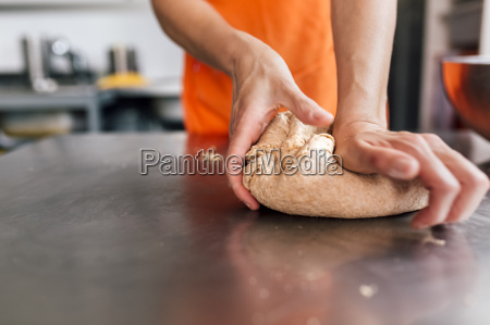 womans hand kneading pizza dough close
