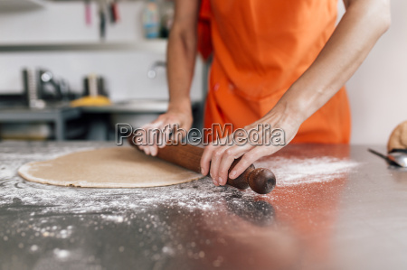 hands of woman rolling out pizza