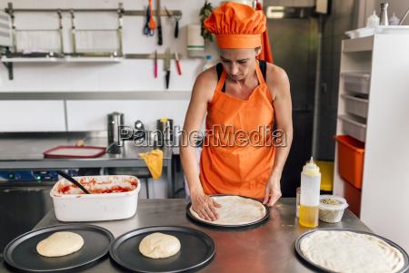 pizza baker preparing dough in the