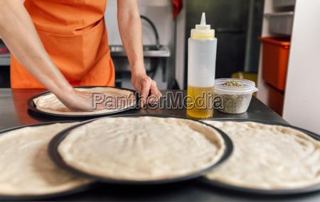 womans hands preparing pizza dough partial