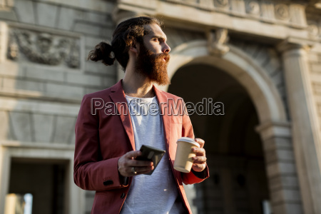 young man with coffee and smartphone
