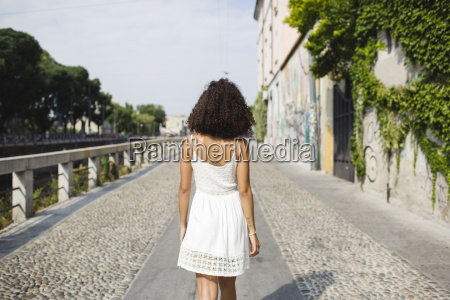 back view of walking young woman