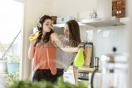 two happy women in kitchen cleaning