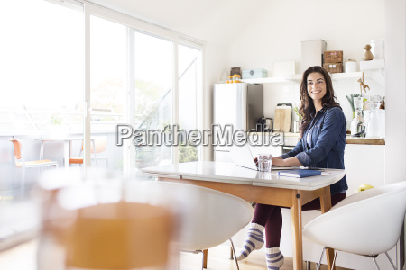 smiling young woman at home using