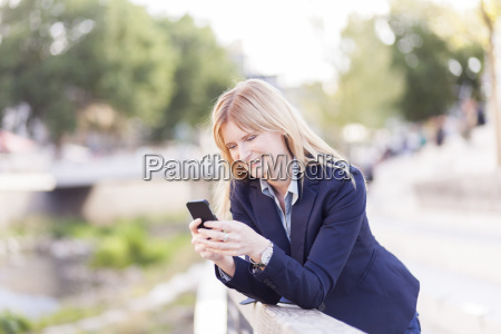 smiling businesswoman leaning on railing looking