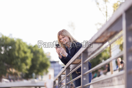 businesswoman leaning on railing looking at