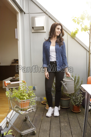 smiling young woman with potted plant