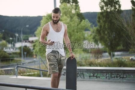 young man in skatepark looking at