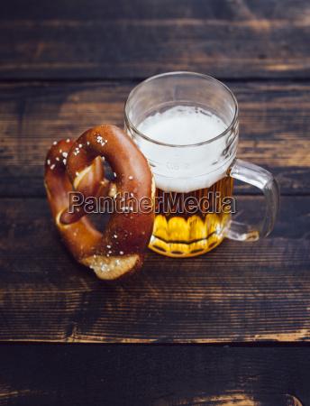 brezeln und glas bier auf dunklem