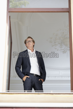 businessman with hands in pockets looking