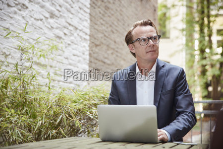businessman sitting with laptop at table