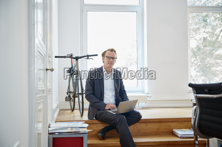 businessman with laptop sitting on steps
