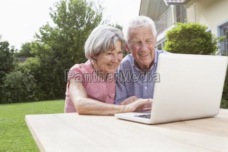 smiling senior couple using laptop in
