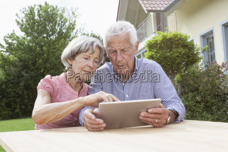 senior couple using digital tablet in